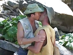 Gay fisherman kisses friend by river