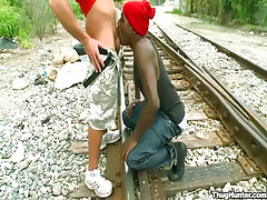 Ebony twink serves white friend on railyard